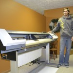 Owner of Spectra Wraps Matt Buller next to his printer at his new office in downtown Henderson.