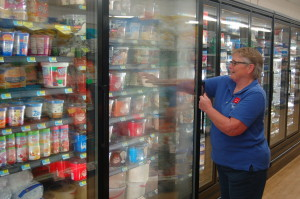 Manager Jackie Nunnenkamp stocks ice cream in the newly remodeled freezer section.